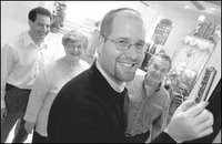 Photo by Tom Hoffmeyer. Rabbi Jason Miller demonstrates how he will place a mezuzah on the doorpost of the sanctuary at Congregation Beit Kodesh in Livonia. Behind him are Jeff Kirsch of Farmington Hills (left); Phyllis Lewkowicz, Livonia and Martin Diskin, Farmington Hills.